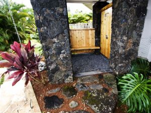 Outdoor lava rock shower with cedar walls and bench